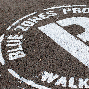 "Road surface marking with the text ""Blue Zones Project"""